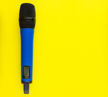 Blue Professional Vocal Wireless Microphone On Yellow Background. Space For Text.