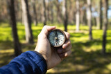 Closeup of hand holding old magnetic compass and showing directions in the forest.