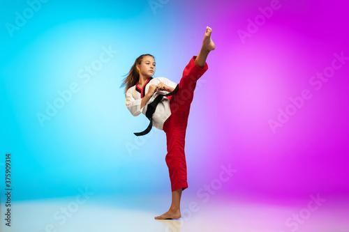 Obrazy Taekwondo   hitting-karate-taekwondo-girl-with-black-belt-isolated-on-gradient-background-in-neon-light-little-caucasian-model-sport-kid-training-in-motion-and-action-sport-movement-childhood-concept