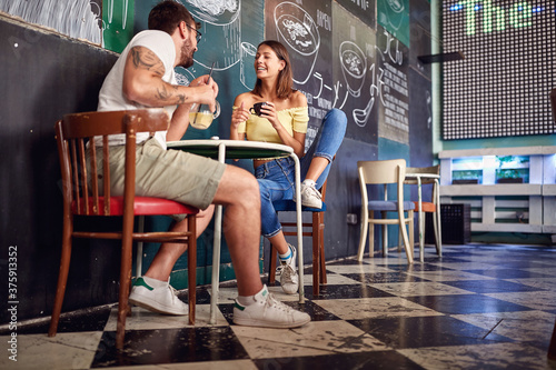 Obraz na plátně Young couple enjoying the drink in a cafe