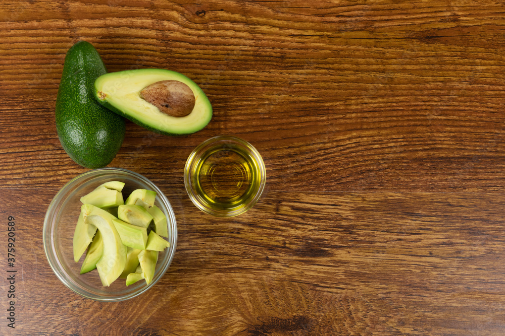 View of two avocados, olive oil bottle and cut avocado in a bowl on wood table background