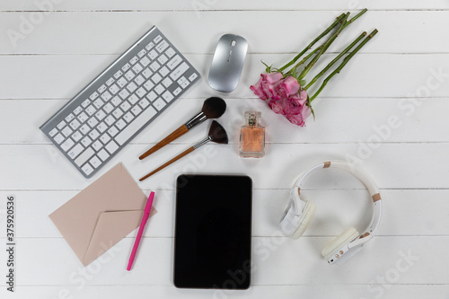 View of a keyword with make up, tablet, flowers and headphones on white wood background