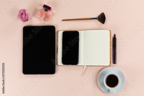 View of school supplies with tablet and phone, cup of coffee, flowers and brush on pink background