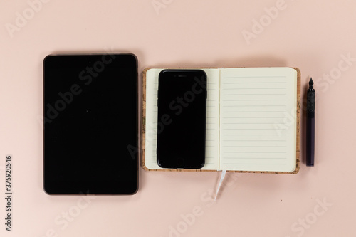 View of a tablet and phone with notebook and pen on pink background
