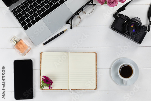 View of a laptop with a camera and a phone, perfume and notebook on white wood table background