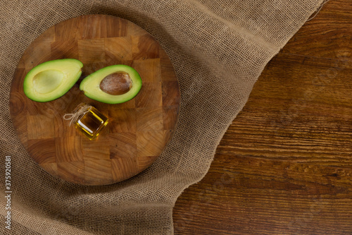 View of an avocado and olive oil bottle on wood table background