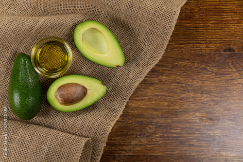 View of two avocados and olive oil bottle on wood table background