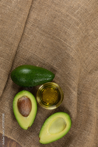 View of two avocados and olive oil bottle on cloth background