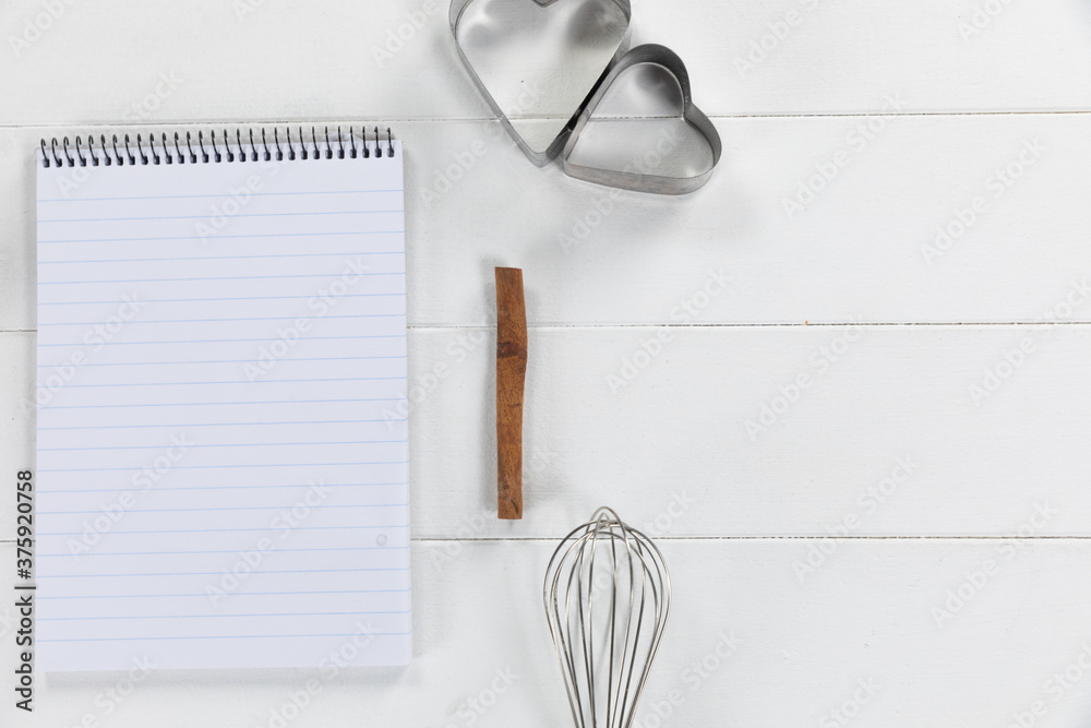 View of a composition with a notebook with cookie cutters and whisker on white wooden surface
