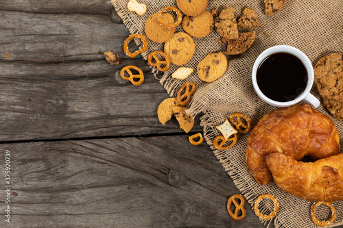 View of cookies, pretzels and croissants put on a table cloth with a cup of coffee on wooden surface