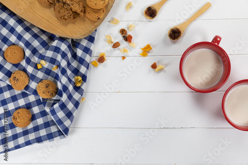 View of cookies, spoons with dried fruits and nuts and two mugs with milk on wooden
