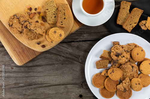 View of some cookies put on a white plate and a wooden cutting board, arranged on on a textured wood