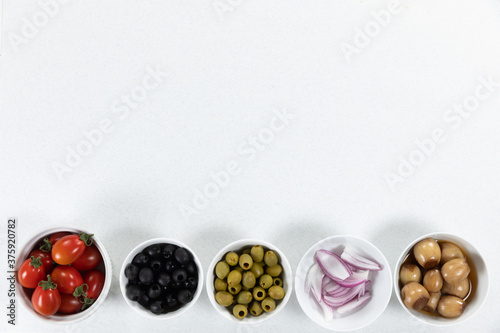 View of a six bowls with fresh tomatoes, olives, nuts and seasoning on plain white surface