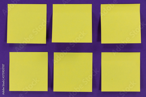 View of six yellow sheets of paper in one size on a plain purple background