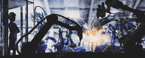 Fotografía Silhouette of modern automation robot arms with Ai assistant technology network concept and smart factory  background