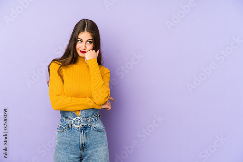 Fotografia Young caucasian woman isolated on purple background who feels sad and pensive, looking at copy space