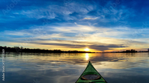 View from bow (prow) of green kayak at colorful sunset over Danube river at autumn time Canvas-taulu