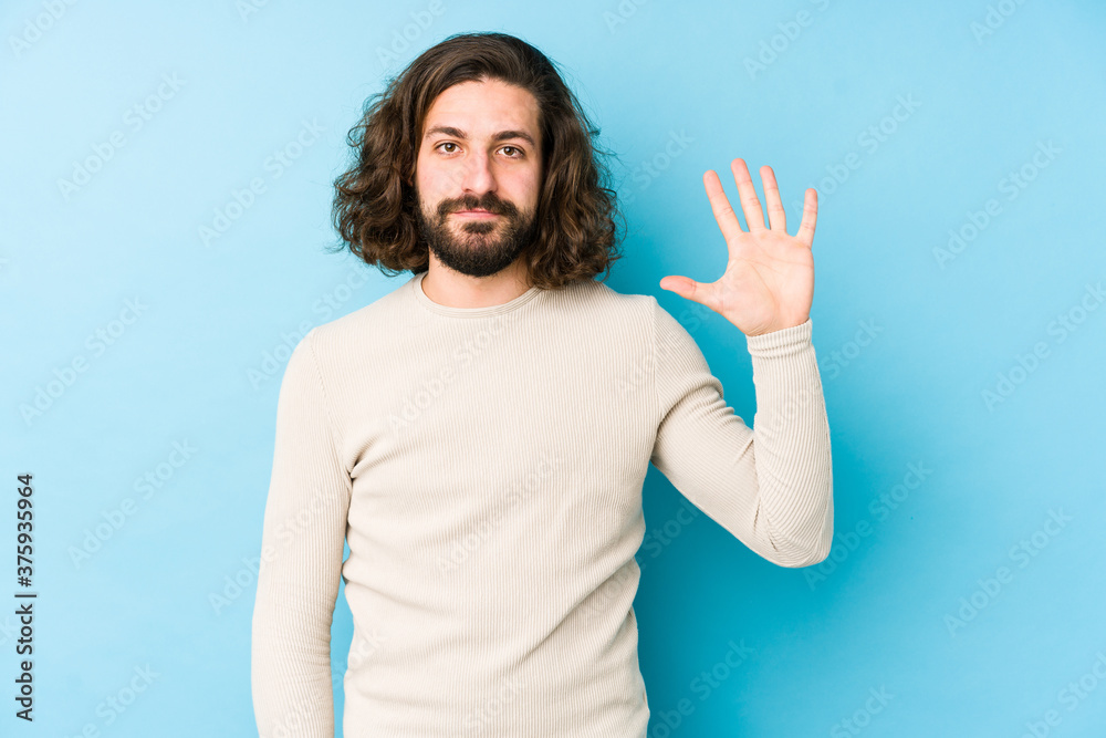 Fototapeta Young long hair man isolated on a blue background smiling cheerful showing number five with fingers.