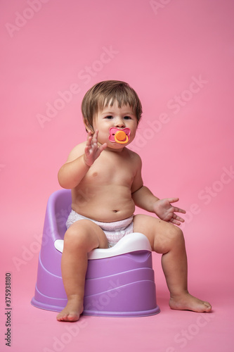 Canvas Print Cute baby in a diaper with a pacifier sitting on a pot