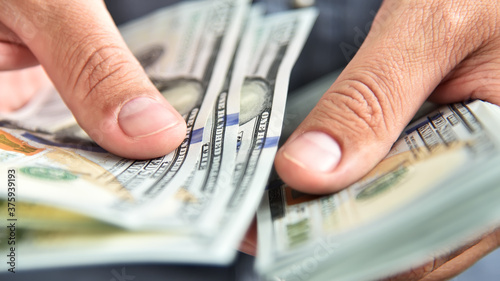 Photo Close up of businessman counts money in hands.
