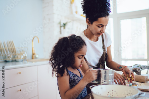 Fotografie, Tablou Little daughter cooking with young mother at table