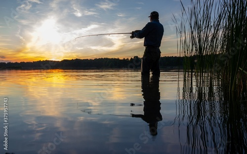 Fotografie, Obraz Angler catching the fish in the lake during sunset