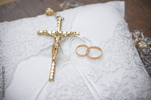 Fotografering gold rings and cross on the wedding cushion