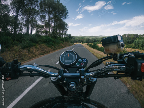 Fotografie, Obraz Riding an old black motorbike with speedometer on a tarmac road from a driver po
