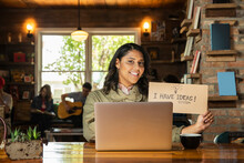 Portrait Of Young Woman Sitting At Table In Coffee Shop Bookstore With Laptop Computer , Holding Hand Made Sign That Reads I Have Ideas