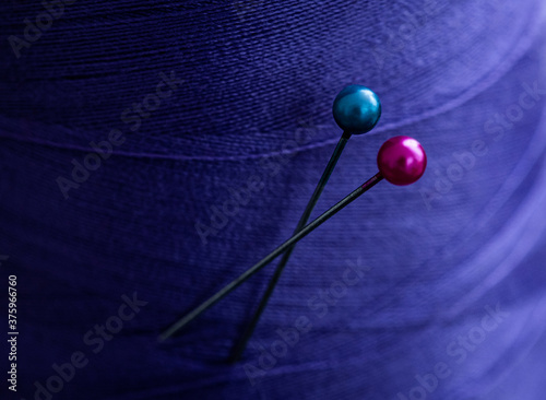 Fototapeta Close up view of sewing pins in blue cloth