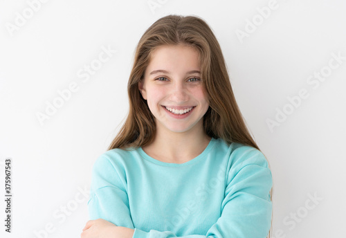 Photo Portrait of smiling teenage girl with long loose hair on white wall background