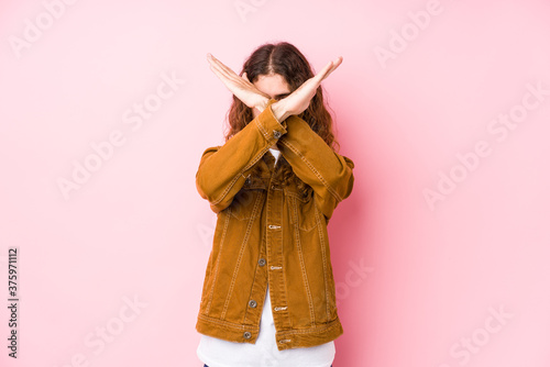 Leinwand Poster Young long hair man posing isolated keeping two arms crossed, denial concept
