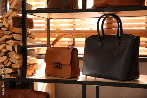 Foto Stylish woman's bags on shelf in boutique