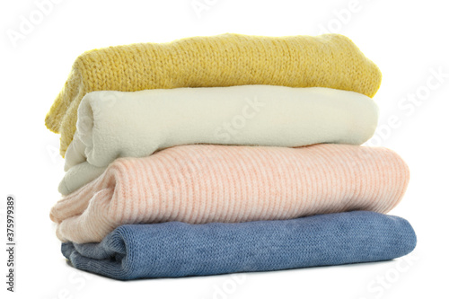 Slika na platnu Stack of different warm sweaters isolated on white