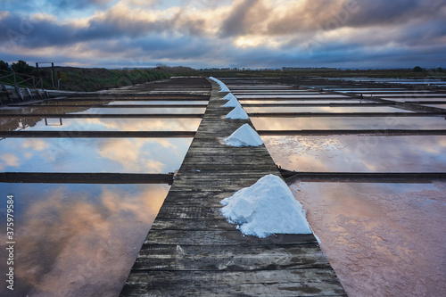 Fototapeta Traditional salt extraction camp (Salinas) with piles of extracted salt at sunri