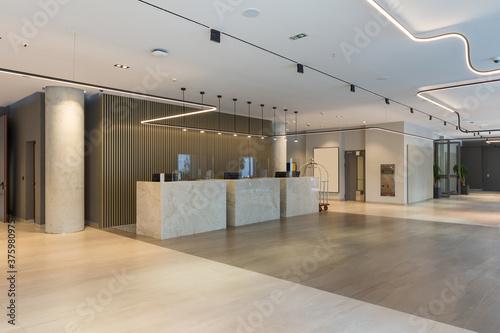 Fototapeta Interior of a hotel lobby with reception desks with transparent covid plexiglass