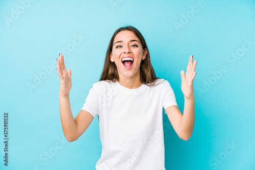Young caucasian woman isolated receiving a pleasant surprise, excited and raising hands.