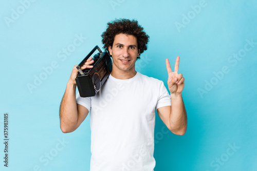 Tela Young caucasian curly man holding a guetto blaster showing number two with fingers
