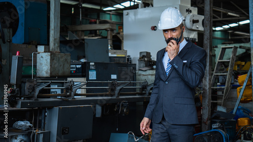 Fotomural industrial manager in suit and wearing white protect helmet, check and control w