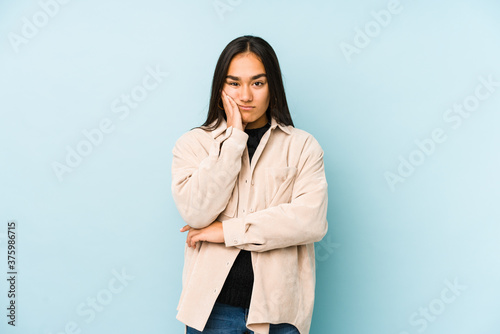 Young woman isolated on a blue background who is bored, fatigued and need a relax day Fototapeta