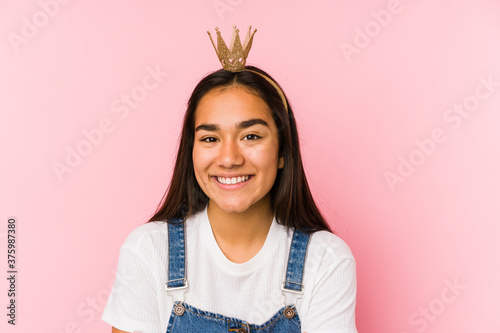Fototapeta Young asian woman wearing a crown isolated laughing and having fun