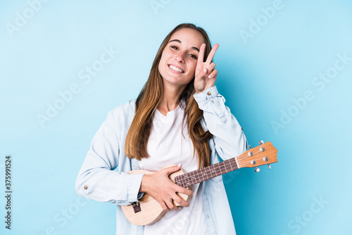 Young caucasian woman holding a ukelele isolated showing victory sign and smiling broadly Canvas Print