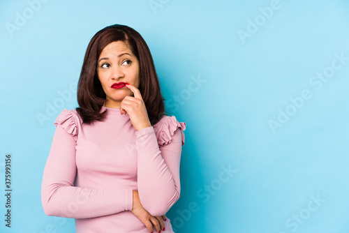 Photographie Middle age latin woman isolated looking sideways with doubtful and skeptical expression