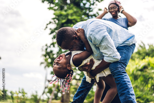 Fototapeta Portrait of enjoy happy love black family african american father and mother with little african girl child smiling and having fun moments good time in summer park at home obraz