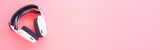 White music headphones on pink background. web banner size.
