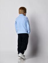 Blond Kid Boy In Sneakers, Black Sport Pants, Blue Turtleneck Sweater Stands Back To Us Walks Away Looking Down