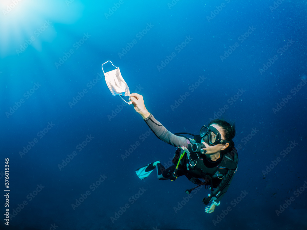 Fototapeta Concept of sea pollution with a scuba diver who picks up a used face mask underwater