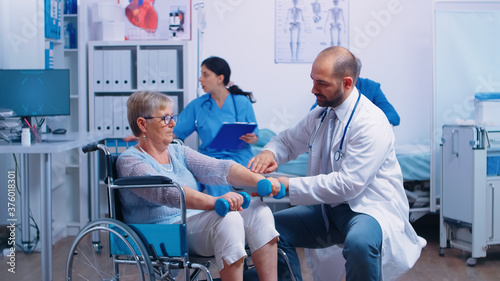 Doctor helping disabled senior patient to recover muscle strength in private modern rehabilitation clinic or hospital Fotobehang