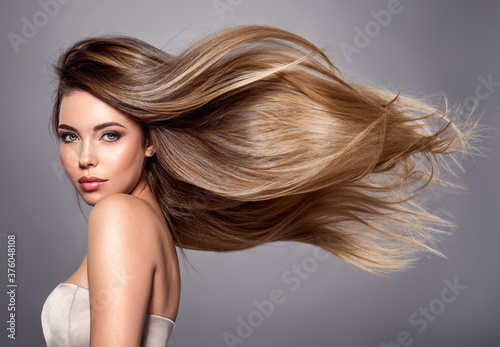 Beautiful woman with long straight hair. Blond girl.