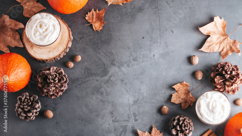 Foto Autumn border with natural pine cones, pumpkins, dried leaves and pumpkin latte on dark grey stone top, top view, copy space